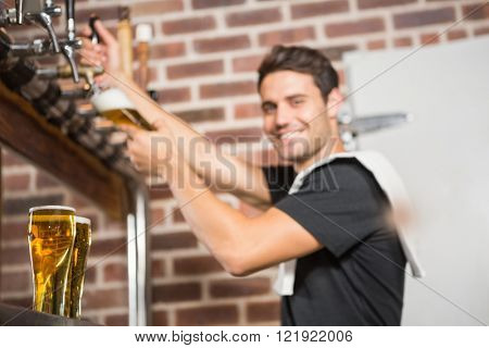Handsome barman pouring a pint of beer in a pub