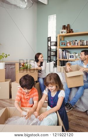 Family unpacking cardboard boxes in living room