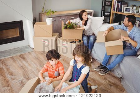 High angle view of family unpacking cardboard boxes in living room