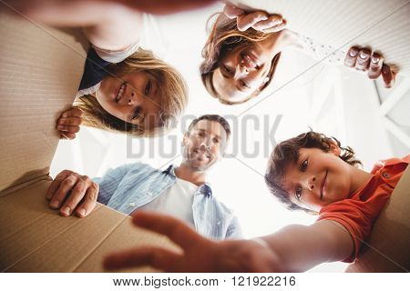Directly below shot of smiling family with cardboard boxes