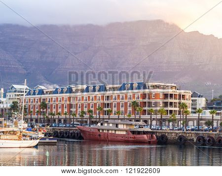 CAPE TOWN SOUTH AFRICA - FEBRUARY 19 2016: Waterfront in Cape Town South Africa overlooked by Table Mountain at sunset.