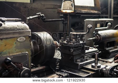 Old metal milling machine in factory closeup.