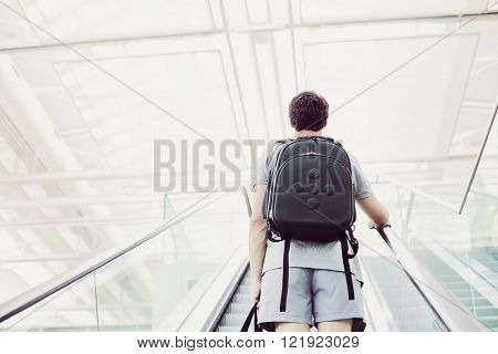 Back view of college student with backpack going up airport escalator holding travel bag in his hand - journey concept