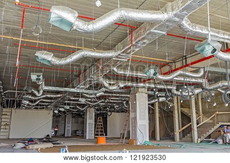 Ventilation pipes in silver insulation material hanging from the ceiling inside new building.