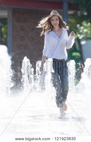 Lovely young woman playing with sparkling water in a park.