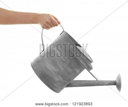 Female hand holding a simple big aluminum  watering can with spout isolated on white background
