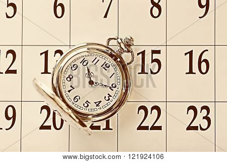 Vintage silver pocket watch laying on calender page with dates, top view