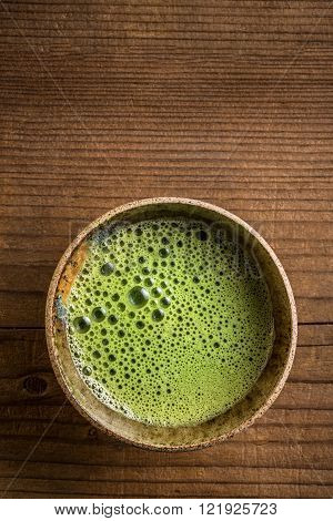 Matcha tea serving in matcha bowl on wooden table