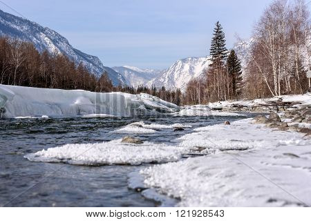 Scenic spring view on the fast mountain river flowing among stones with the banks of the ice and snow on background of mountains forest and blue sky
