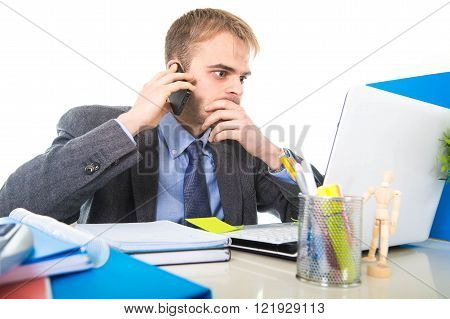 young Caucasian attractive businessman worried and tired talking on mobile phone sitting at laptop computer office desk working in stress overworked and frustrated isolated on white background