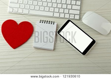 Computer peripherals with red heart, notebook and mobile phone on light wooden table
