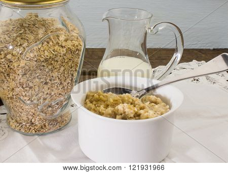 Raw rolled oats and cooked oats on table
