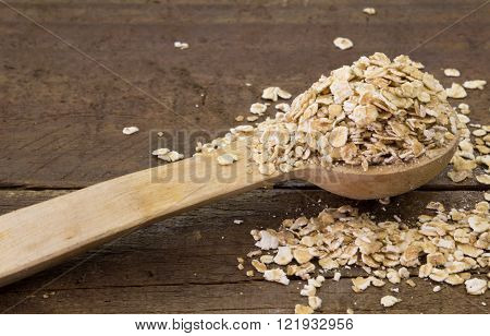 Wooden spoon with raw rolled oats on wood background