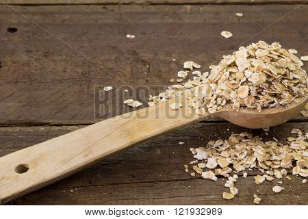 Close up of a wooden spoon of raw rolled oats isolated on wood background