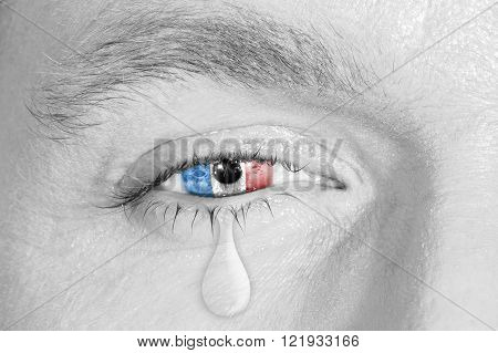 Crying eye with France Flag iris on black and white face. concept of sadness for France pain, war and terrorist attack, patriotic metaphor