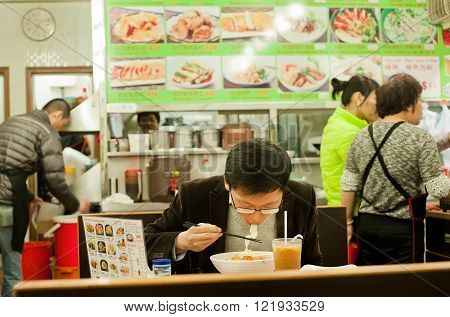 HONG KONG, CHINA - FEB 8: Lonely young man eat food with hunger inside small and simple Chinese restaurant on February 8, 2016. More than 47 million tourists visit Hong Kong annually