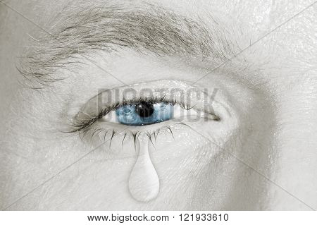 Crying blue eye on black and white face. concept of sadness, fear, love pains, mental depression disease,  eyewash and eye health