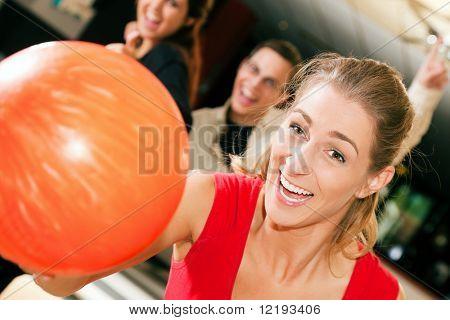 Grupo de cuatro amigos en una bolera, diversión, tres de ellos que anima uno encargado de thr