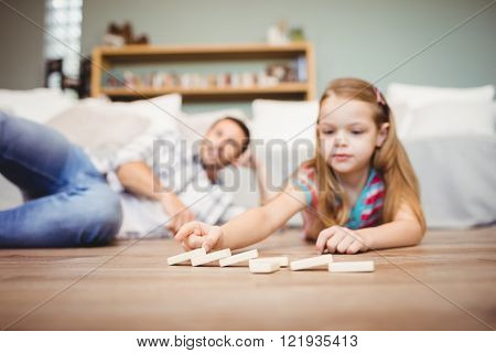 Close-up of girl arranging domino while father lying on hardwood floor at home