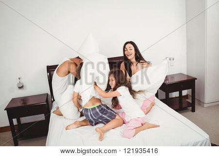 Cheerful family pillow fighting on bed against wall at home