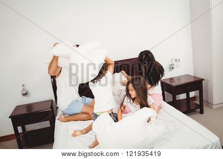 Family pillow fighting on bed at home