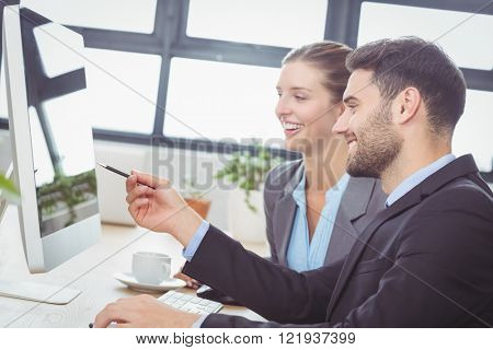 Businessman explaining female colleague while pointing on computer monitor at desk in office