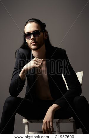 Handsome brunet man in black suit and sunglasses. Fashion studio shot.