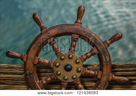 Nautical Detail Of A Ship's Wheel Against Tropical Ocean Water
