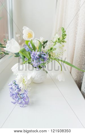 sunny day on the windowsill is a white vase with a bouquet of flowers from tulips and hyacinth