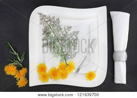 White porcelain table setting with two plates, antique sliver fork, linen napkin with dandelion flowers, rosemary and  bronze fennel herb over slate background.