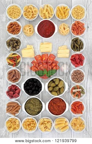 Large italian food ingredient sampler with pasta, pesto, ragu, olives, chorizio and garlic over distressed white wood background.