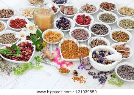 Alternative herbal medicine flower and herb selection with honey and bee and pollen over distressed wooden background.