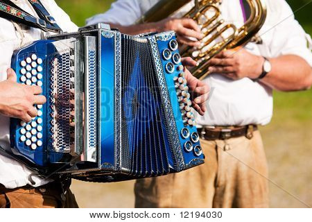 Banda tradicional bávaro con el acordeón y la tuba jugando sólo marchando de la música, las manos de músicos