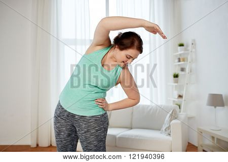 fitness, sport, exercising, training and lifestyle concept - smiling plus size woman stretching at home