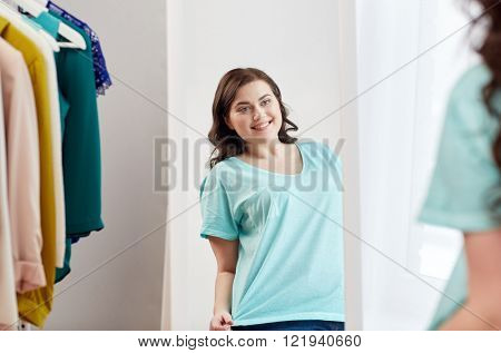 clothing, fashion, style and people concept - happy plus size woman choosing clothes and posing at mirror at home wardrobe