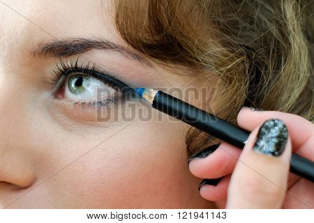 Girl makeover. The coloring of the eye pencil. Cosmetics for the eyes. ** Note: Shallow depth of field