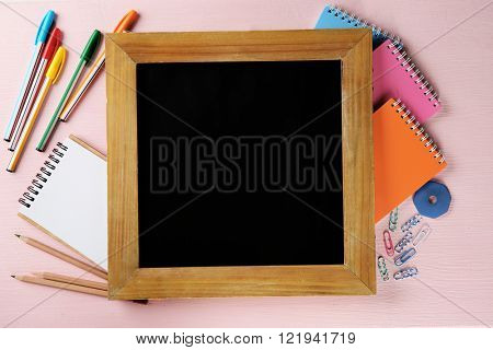 Small school blackboard with stationery on pink wooden background
