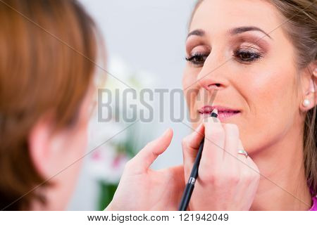 Beautician applying lip color on woman in beauty parlor