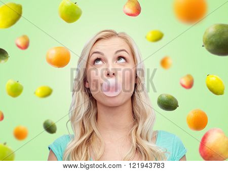 summer, healthy eating, emotions, expressions and people concept - happy young woman or teenage girl chewing gum over green background with fruits