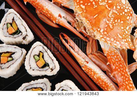 Maki Rolls and California rolls made of fresh raw Salmon, Tuna and Eel . on black dish with boiled crab . Maki Sushi and Nigiri