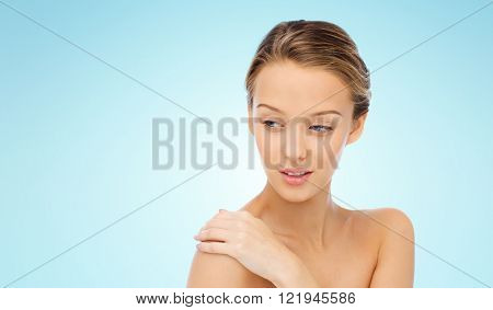 beauty, people, body care and health concept - smiling young woman face and hand on bare shoulder over blue background
