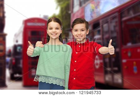childhood, travel, tourism, gesture and people concept - happy smiling boy and girl hugging and showing thumbs up over london city street background