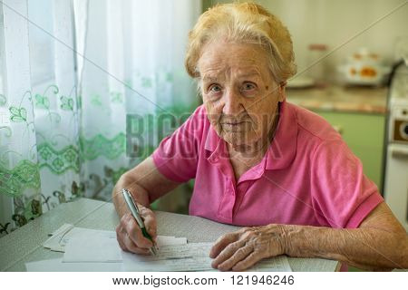 Elderly woman with bills to pay utilities.
