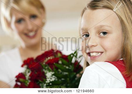 Girl child giving flowers to her mother for mother's day, a bunch of red roses