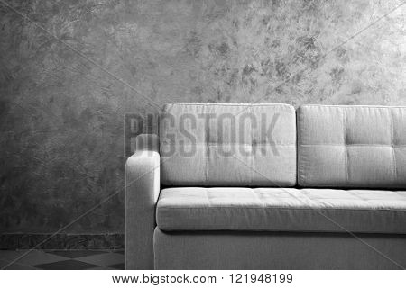 Comfortable sofa against grey wall in the room, close up