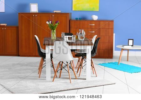 Modern living room. Furniture set with table and chairs. Bouquet of beautiful white and purple tulips on the table