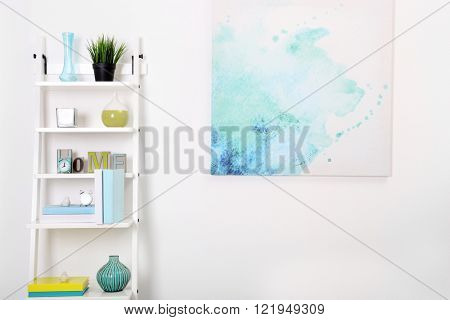 White bookcase against wall with bright picture in the room