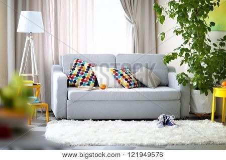 Living room interior with sofa, lamp and green tree