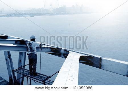 A construction worker in the repair of the bridge scaffolding
