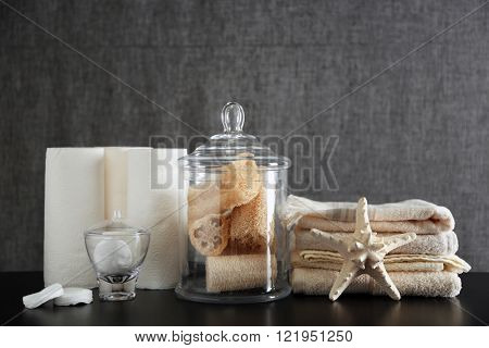 Bathroom set with towels, wisps and sponges on grey background